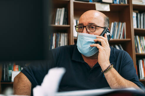 Businessman wearing protective face mask while talking on smart phone in office during COVID-19 - ABAYF00001
