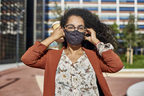 Young woman wearing protective face mask standing in city on sunny day - VEGF03128