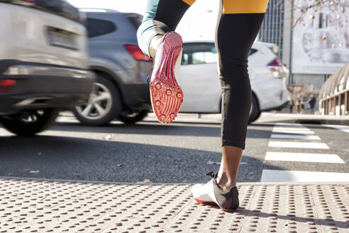 Young woman wearing sports shoe crossing road in traffic while running in city - GGGF00058
