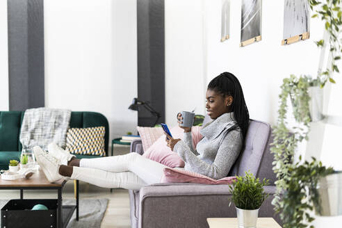Woman drinking coffee while using smart phone sitting on sofa in living room at home - GIOF09610