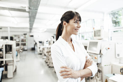 Thoughtful female engineer looking away while standing with arms crossed in industry - JOSEF02176