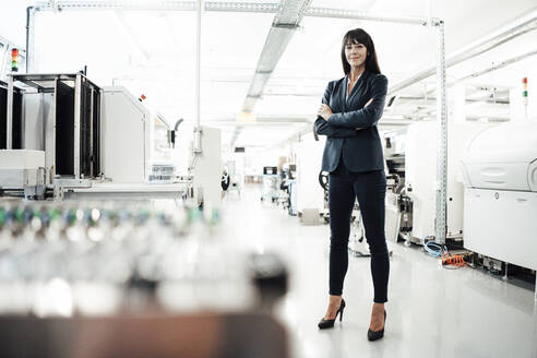 Confident mature businesswoman standing with arms crossed at industry - JOSEF02218