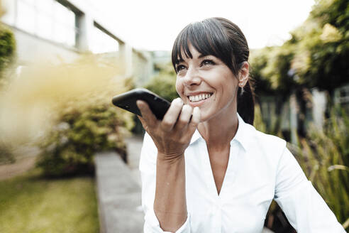 Happy businesswoman looking away while talking on mobile phone - JOSEF02239