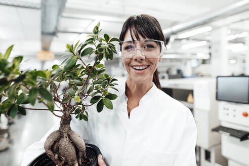 Smiling female scientist holding potted plant at laboratory - JOSEF02299