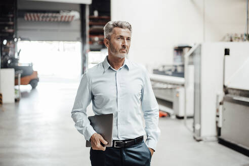 Mature businessman with digital tablet looking away while standing in factory - JOSEF02356