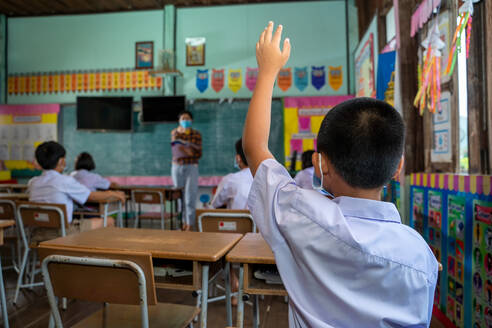 Asian student with hands up during learning in classroom at elem - CAVF90524