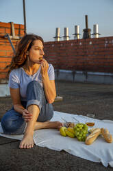 Young woman having fruits during picnic on rooftop - NGF00703