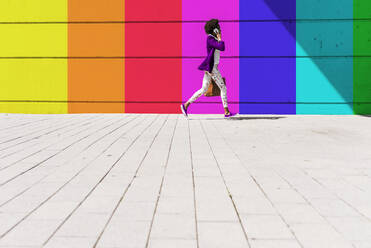 Young woman talking on smart phone while walking by colorful wall during sunny day - UUF22059