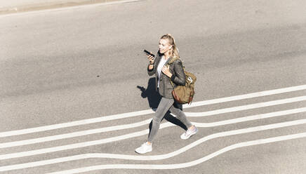 Young woman talking through smart phone while walking on street during sunny day - UUF22062