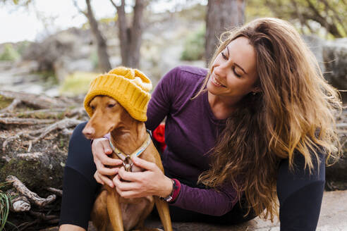 Smiling woman sitting with dog in forest at La Pedriza, Madrid, Spain - MRRF00683