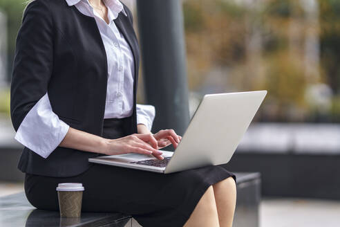 Businesswoman using laptop while sitting on bench outdoors - GGGF00105