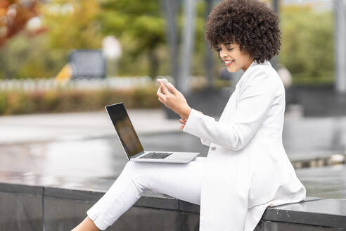 Businesswoman with laptop using mobile phone while sitting on bench outdoors - GGGF00108