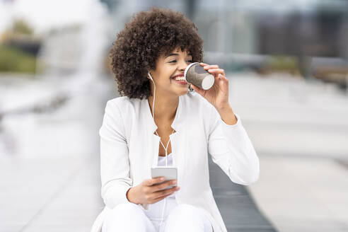 Smiling businesswoman with mobile phone drinking coffee while sitting at city - GGGF00120
