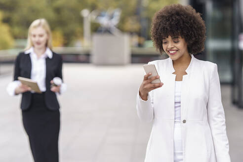 Businesswoman using mobile phone while standing with colleague in background on footpath - GGGF00126
