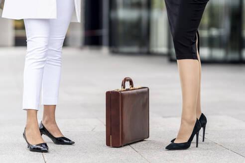 Businesswomen standing by briefcase on footpath - GGGF00129