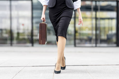 Young businesswoman wearing high heels walking with briefcase on footpath - GGGF00132