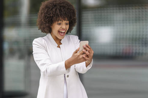 Happy businesswoman looking at mobile phone while standing outdoors - GGGF00156