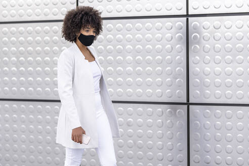 Businesswoman wearing face mask while walking against silver wall - GGGF00180