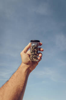 Man holding small marijuana jar against sky - ACPF00874