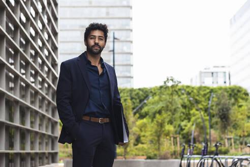 Male entrepreneur with hand in pocket holding folder in city - PNAF00064