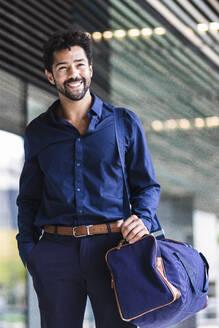 Smiling entrepreneur with bag standing in city - PNAF00106