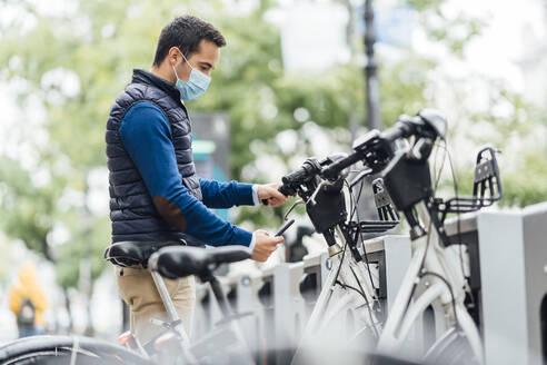 Young man using smart phone at bicycle parking station during coronavirus - CJMF00363