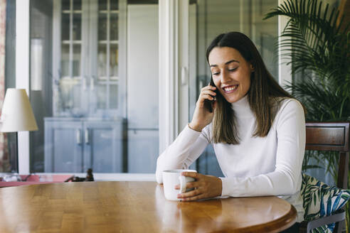 Smiling woman with coffee cup talking on mobile phone while sitting at home - ABZF03429