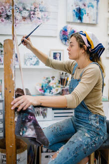 Side view of female artist sitting near easel and drawing colorful picture with paints while working in creative workshop - ADSF17605