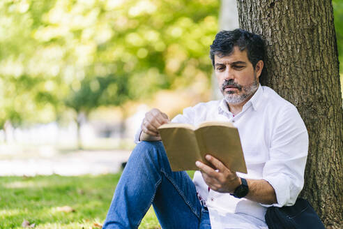 Mature man reading book while leaning on tree trunk in public park - DGOF01651