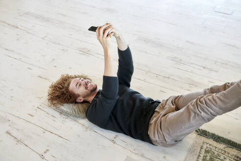 Smiling man taking selfie through smart phone lying down on floor at home - FMKF06677