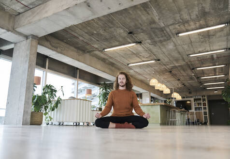 Man meditating while sitting on floor in living room at home - FMKF06725