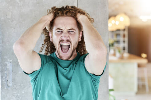 Man in aggression shouting while standing against column at home - FMKF06755