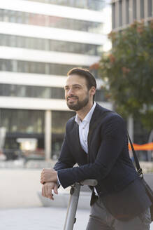 Smiling businessman on electric push scooter in city - HMEF01160
