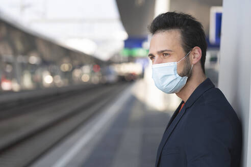 Male entrepreneur looking away while wearing protective mask on railroad station platform - HMEF01181
