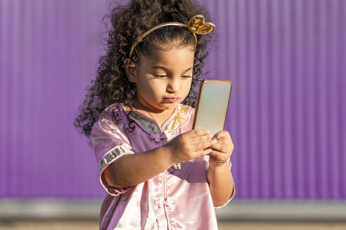 Cute girl puckering while using mobile phone standing against purple wall - GGGF00187