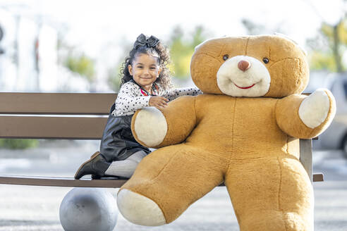 Smiling girl sitting with teddy bear on bench - GGGF00193