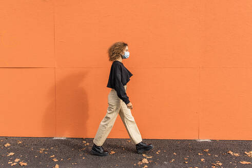 Young woman wearing face mask walking against orange wall - MEF00001