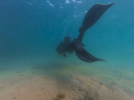 Rear view of man diving in sea - RSGF00421
