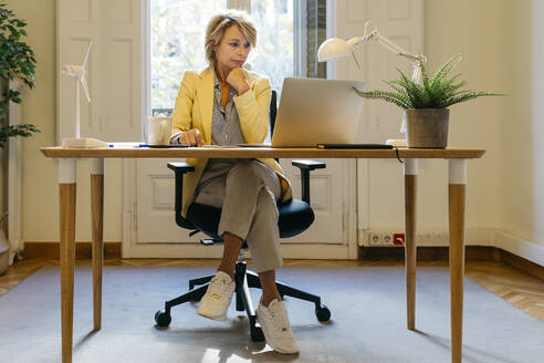 Thoughtful female engineer working on laptop while sitting in office - JRFF04932