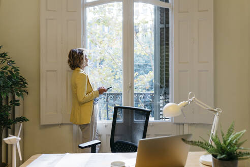 Female entrepreneur looking through window while holding smart phone in office - JRFF04941