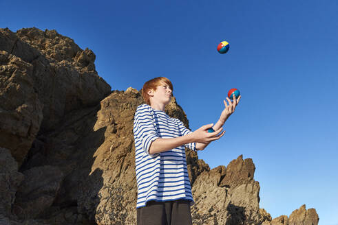 Boy juggling balls while playing against clear sky - JEDF00337