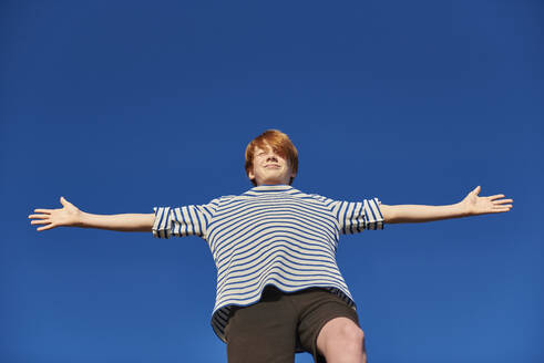 Boy standing with arms outstretched against clear sky - JEDF00340
