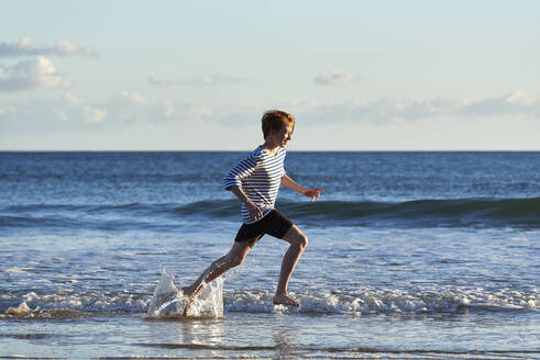 Smiling boy running in water at beach - JEDF00343