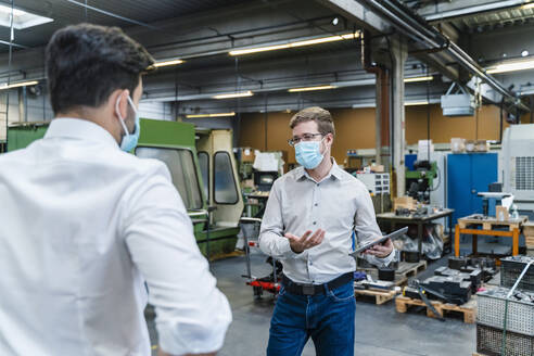 Male entrepreneurs discussing while wearing protective face mask in industry - DIGF13258