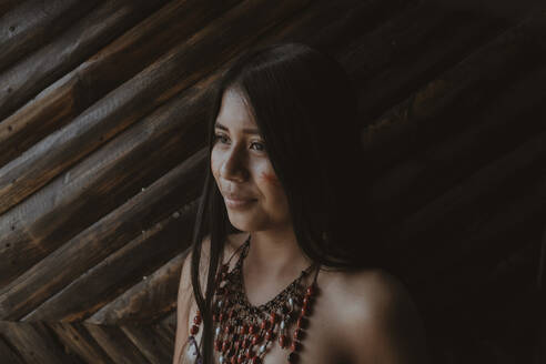 Thoughtful young Guarani woman looking away against bamboo wall, Misahualli,  Ecuador - DSIF00206
