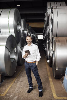 Smiling businessman with hand in pocket holding digital tablet while standing in industry - GUSF04743