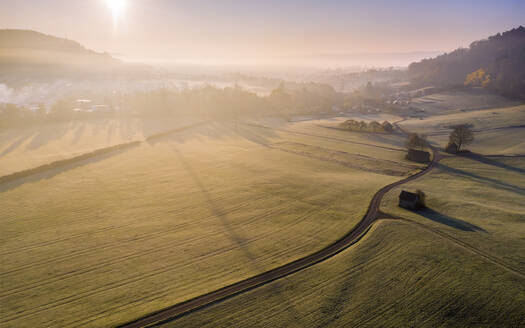 Drone view of countryside fields at foggy autumn sunrise - STSF02674