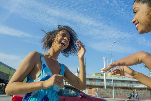 Young woman laughing while looking at female friend in city on sunny day - AJOF00623