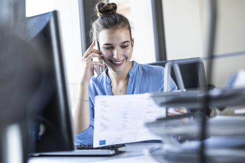 Businesswoman talking on mobile phone while sitting at office - UUF22075