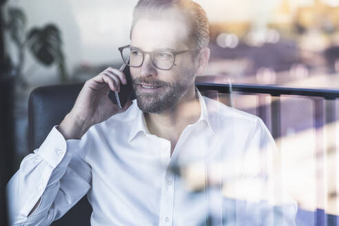 Smiling businessman talking on mobile phone while sitting at office - UUF22093